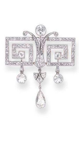 Early Art Deco or Belle Epochh diamond brooch. A décor de grecques sertie de petits diamants retenant trois diamants plus importants en pampilles, monture en or et platine, vers 1910 Porte un no. 36798 #DiamondBrooches #artdecojewelry #antiquejewelry