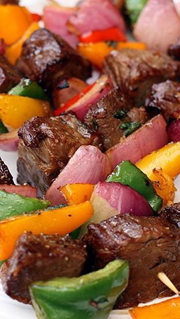 MARINATED STEAK KEBABS   ~  1/2 c. low-sodium soy sauce...1/2 c. peach juice...1/2 c. vegetable oil...1 T. dried onion flakes...2 cloves garlic, minced...fresh ground black pepper, to taste...1-1/2 lbs. top sirloin steak, cut in 1'' chunks...1 green bell pepper, sliced into large chunks...1 red bell pepper, sliced in large chunks...1 red onion, sliced into large chunks...Wood or bamboo skewers