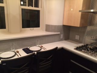 smoke grey glass subway tile backsplash with stainless steel tile behind the stove https