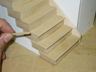 applying nose trim to a dollhouse staircase