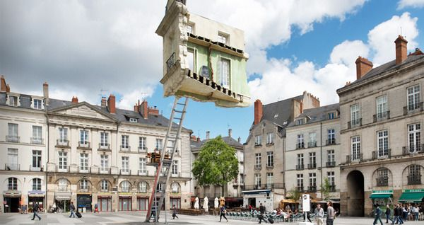 "Leandro Erich - ""L'ultime Déménagement,"" is a sculpture of a giant piece of a building facade, anchored to the ground by nothing more than a ladder."