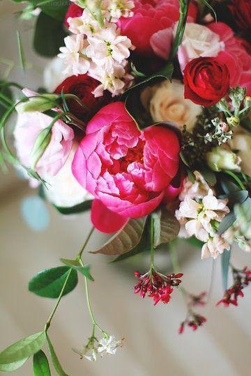 detail of loose unstructured bridal bouquet of coral charm peonies, red ranunculus, Vendala roses, hot pink ranunculus, light pink lisianthus, jasmine vine, lemon leaf, peach stock & seeded eucalyptus wrapped in cream muslin ribbon