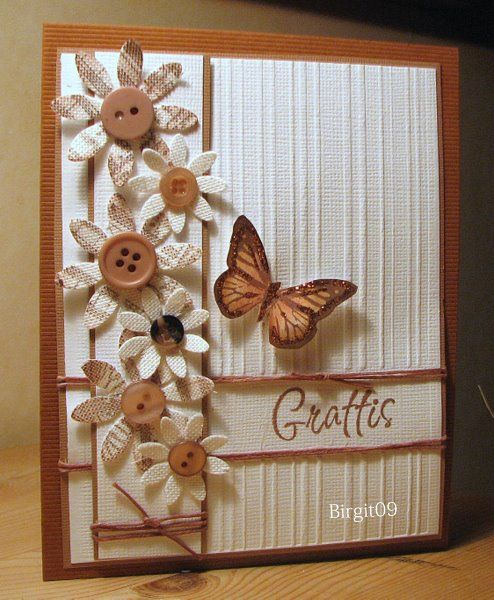 love the browns in this card with the paper flowers and buttons not sure the company but i know CTMH sells wooden buttons and paper flowers that look like this!