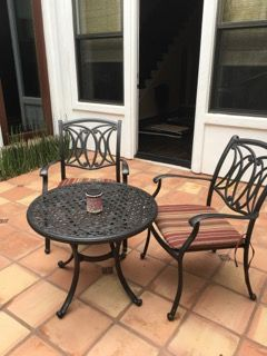 THREE PIECE PATIO FURNITURE SET INCLUDES TWO ARM CHAIRS AND A BISTRO TABLE WITH ALLEN AND ROTH CUSHIONS. (LIGHT ON TABLE FOUND IN SEPARATE LOT)