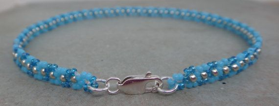 This Wave Daisy Chain ankle bracelet is beaded with tiny Turquoise seed beads alternating with Capri blue rainbow and accented with Duracoat Galvanised Silver seed beads. It is finished off with a silver plated Lobster Claw clasp. This anklet has a delicate wave daisy pattern. The