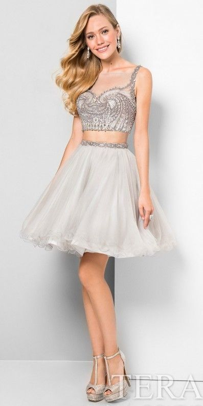 Terani Couture Illusion Tulle Fit and Flare Two Piece Cocktail Dress. Dazzle the crowd in this Illusion Tulle Fit and Flare Two Piece Cocktail Dress by Terani Couture. This must have style features an illusion neckline, a matching illusion open back, and a rhinestone beaded bodice. This playful style also features a layered tulle skirt creating a fi t and flare silhouette. Pair this style with sky high heels and drop earrings for a gorgeous look. Additional Information Illusion neckline…