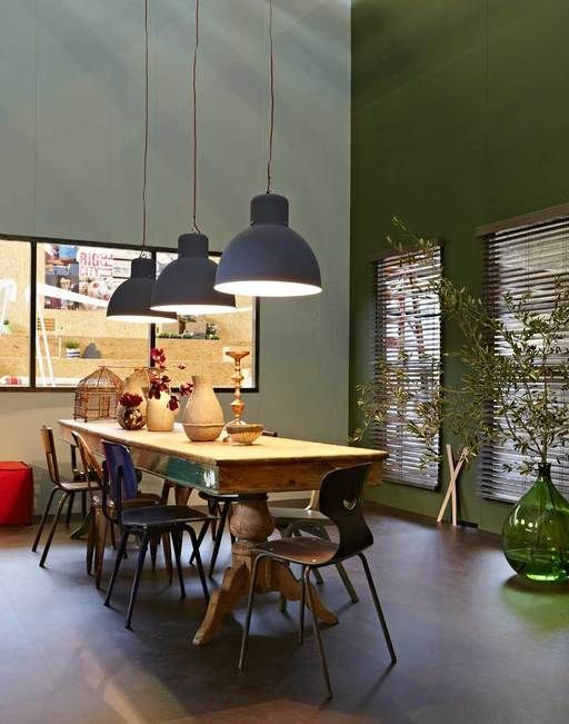 Een oude, lange tafel met verrassende bolpoten, een verzameling verschillende stoelen en een paar stoere lampen vormen de basis voor urenlang tafelplezier.