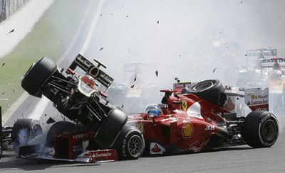Lotus driver Romain Grosjean of France, top left, crashes with Ferrari driver Fernando Alonso of Spain, during the first lap of the Belgium Formula One Grand Prix in Spa-Francorchamps circuit, Belgium, Sunday, Sept. 2, 2012.