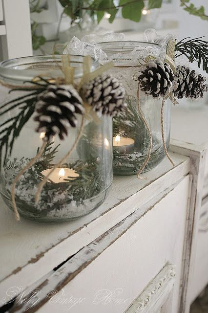 Tea lights in a bed of pine needles, pine cones attached to top of clear jar. Charming soft backlight.