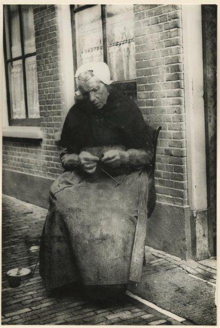 Scheveningse vrouw in klederdracht breiend voor haar huisje zij draagt een muts met klappen, een ijzer met stukken, een zwarte wollen omslagdoek met gehaakte franje. ca 1930 #ZuidHolland #Scheveningen