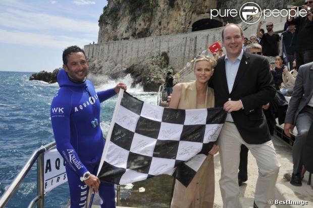 Le prince Albert de Monaco et son épouse Princesse Charlene prennent la posele vendredi 24 mai 2013 avec Pierre Frolla, parti chercher le drapeau à damier du Grand Prix de Monaco à 70 mètres de profondeur. Signés par les pilotes de F1, celui-ci sera vendu aux enchères au profit d'une association, Aequalia.