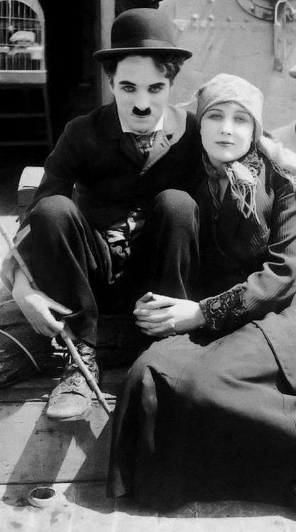 "Charlie Chaplin (1889-1977) & his leading lady Edna Purviance (1895-1958)   Photo taken while aboard boat used in his film ""The Immigrant"" (Spring 1917)"