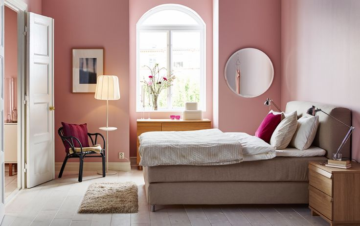 A large bedroom with a beige double bed with an upholstered headboard and bed textiles in beige and white.