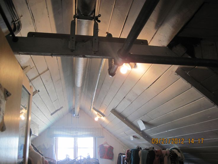 Closer up of the attic ceiling, reinforced with steel beams, and showing a bit of the pipes, and charming painted wood slat facade over the log frame....