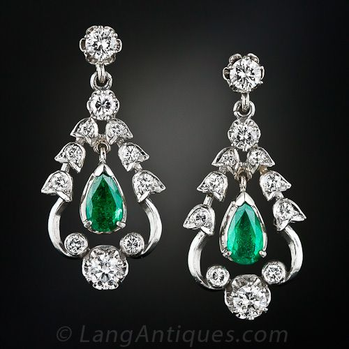 A festive and fanciful pair of emerald and diamond drop earrings crafted in 14 karat white gold during the latter-twentieth century in homage to late nineteenth-century/early twentieth century style. A matched pair bright green pear shape emeralds swing and sway inside a sparkling and curvaceous bright-white diamond frame which, in turn, dangles from a single buttercup set diamond.