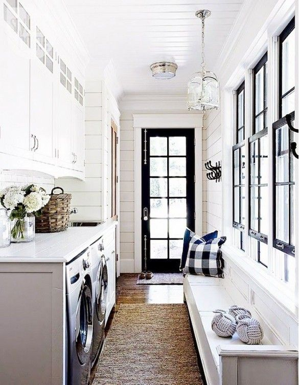 White cabinets, black accent windows, plaid cushion, white bench, straw tan rugs, basket, vase of flowers