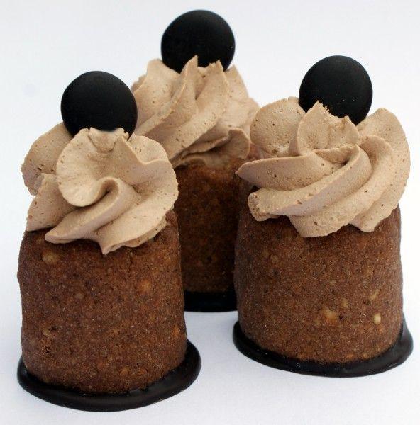 """Krém nastříkněte pomocí sáčku se zdobičkou do každého """"komínku"""", nahoře vytvořte pusinku z pařížské šlehačky a ozdobte ji peckou čokoládové polevy."""