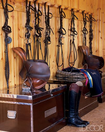 At Home with Badgley Mischka Hermès and Frédéric Butet saddles and bridles and mahogany show trunks in the stable's tack room.