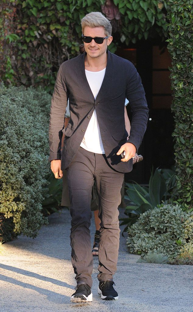 A blond Orlando Bloom steps out in a chic fall outfit, donning classic wayfarer shades.