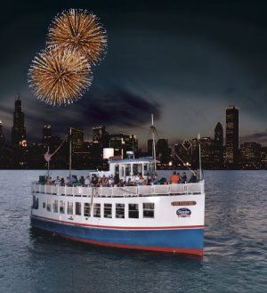 The Cap Streeter in the Chicago Harbor with fireworks and the skyline behind.  chicago fireworks cruise