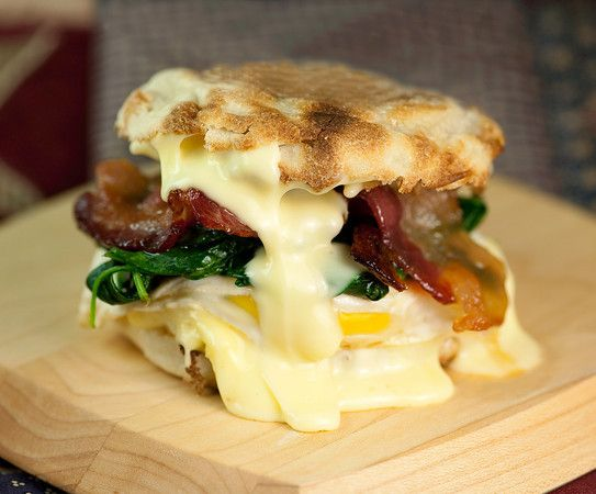 egg, bacon, spinach and brie sandwich on an english muffin