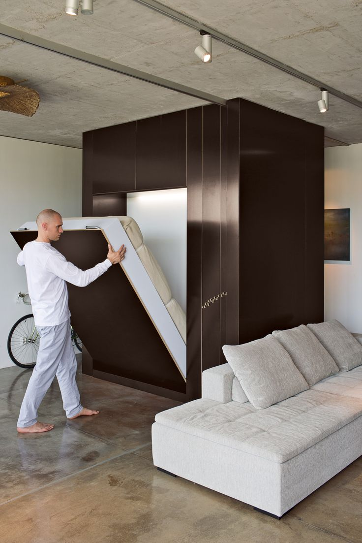 """""""The Cube,"""" as it is known, transforms into a room, then back into a big box when closed. By lowering the custom Murphy bed and rolling a sliding plywood door, Aleksander Novak-Zemplinski creates an insta-guestroom in his small, industrial-style Warsaw loft. photos by: Andreas Meichsner"""