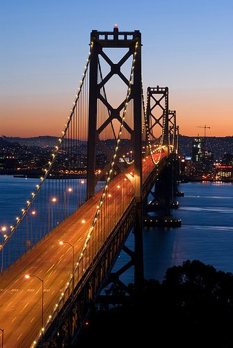 Bay Bridge, San Francisco at dusk. I love my bridge. I love crossing it into the city (san francisco) as a kid, because it meant I was home. Soon as I saw the TransAmerica building, I know I was exactly where I was supposed to be.... HOME.