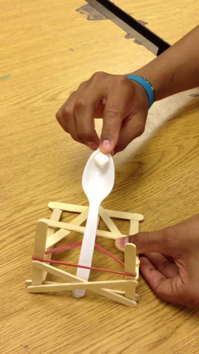 catapult design by a 7th grade student. 12 Popsicle sticks, a rubber band, a plastic spoon and some hot glue. Assignment: design a catapult capable of lobbing mini marshmallows into your neighbor's castle. Mini marshmallows are ideal for a mock medieval siege because they are 100% safe of they hit you.