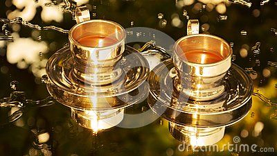 Golden mirror images of two filled coffee cups on transparent reflective surface.