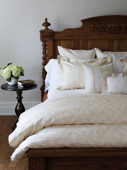 Crisp and cleancut with a romantic touch - beautiful bed / headboard.  Round bedside table.  Fresh flowers at bedside.  White / neutral bed linens.