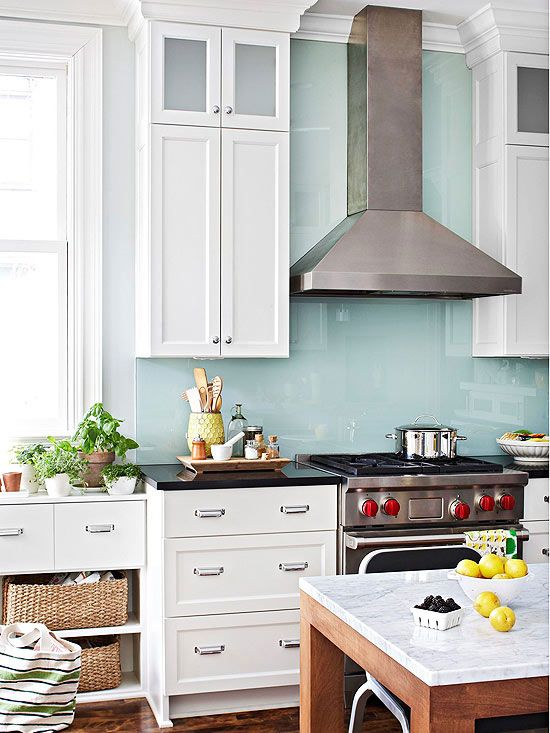 A single sheet of glass, painted on the back, lends color and easy-clean protection behind this range. The glass extends from the countertop to the ceiling as a simple, shining backdrop for the sculptural hood.