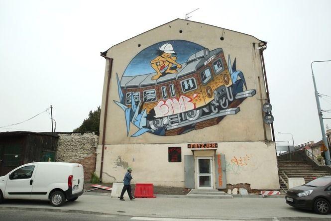 mural powstał wramach festiwalu All My City. Praca na ścianie uzbiegu ulic Kunickiego iPocztowej przedstawia pomalowany pociąg ijadącą na jego dachu postać zpuszką farby wręku.