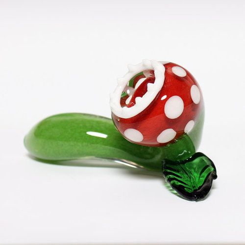 "Mario Piranha Plant Pipe Combine two of your favorite things with this Mario themed glass pipe! This Pyrex glass pipe is 4"" with red/white/green pattern with leaf kickstand. Vivid inside out color patterns make this pipe truly unique and one of a kind. Sold on Etsy."
