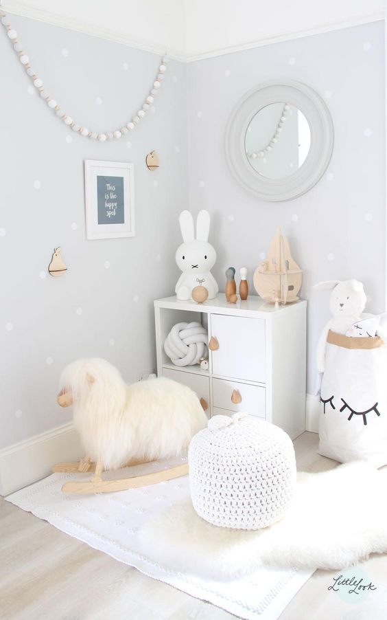 neutral nursery with light blue and white polka-dot wallpaper, white accessories and white rug, light wooden floors