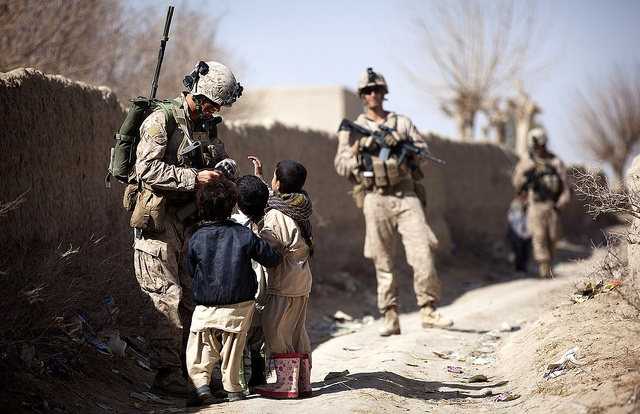 Lance Cpl. Galen Murphy-Fahlgren, a 22-year-old anti-tank missileman with Combined Anti-Armor Team 2, Weapons Company, 3rd Battalion, 3rd Marine Regiment, and a native of Canton, Mich., hands candy to a group of Afghan children during a partnered security patrol with Afghan Border Police here, Jan. 30. The ABP is younger and significantly smaller than the Afghan National Army and police forces, but its mission is vital as Afghan forces prepare to assume lead security responsibility in…