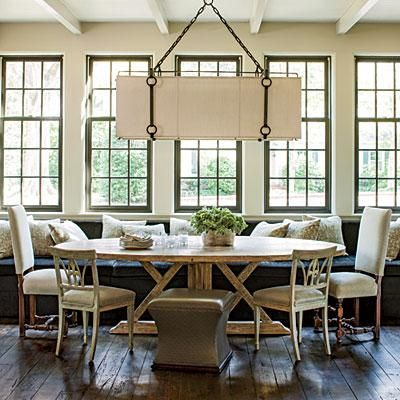 Spread Out | This table's soft oval shape, distinctive base, and light finish are even more striking when juxtaposed with the dark upholstery and sharp angles of the 14½-foot-long banquette. Three other seating styles offer variety to the room, while an enormous chandelier with iron detailing draws the eye up. | SouthernLiving.com