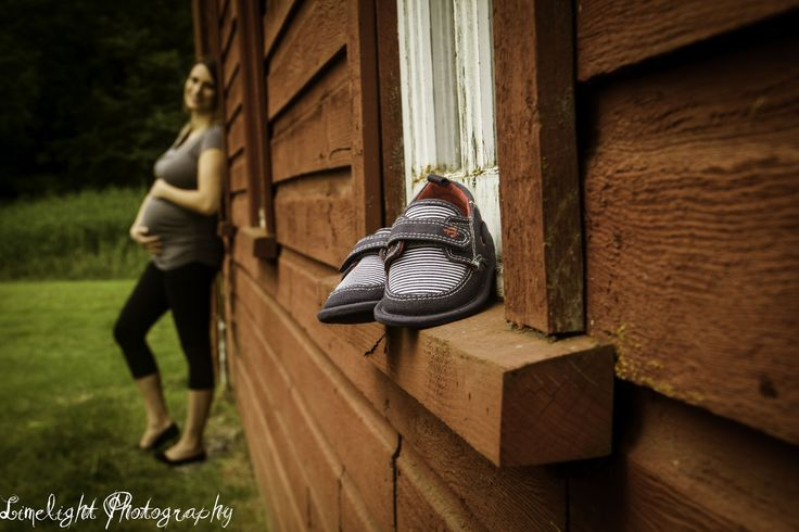 love the baby shoes with the mom in the background shot on a red barn.