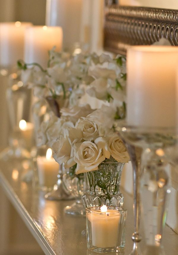 How simply stunning this is.  Just Cream roses, clear glass and soft white candles, but the fact that they are MASSED is what gives them so much impact.