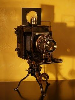 Frozen in Time Take a antique Graflex press camera mounted on a antique Christmas Tree stand.  A pair of calipers and a couple vintage camera lenses for viewing magnification. An antique radio tube and a custom pendulum from a wood watch crystal holder.. U have a wonderful clock!