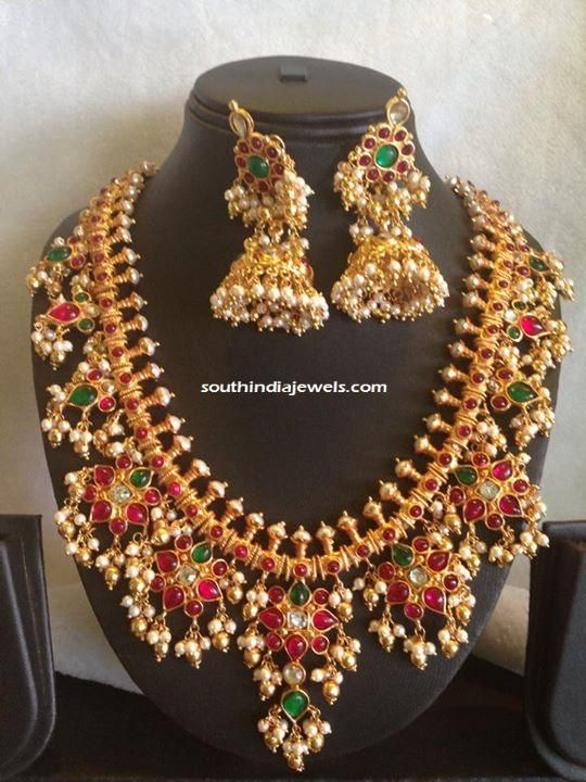 Classic gold plated guttapusalu necklace studded with pearls, emeralds and rubies. For inquiries please contact Queen Jewels Emporium,+91 422 4206118.