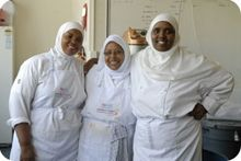Three female muslim volunteers smiling at the camera
