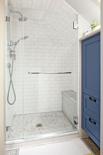 A skylight over the storage cabinet in this master bath ushers in sunlight to keep the shower area airy and bright. A 10-inch-deep marble-covered bench provides a perch.