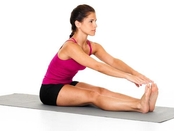 The correct way to stretch your hamstrings: Sit at reach. (Standing and touching your toes puts 600 pounds of pressure on your spine!)