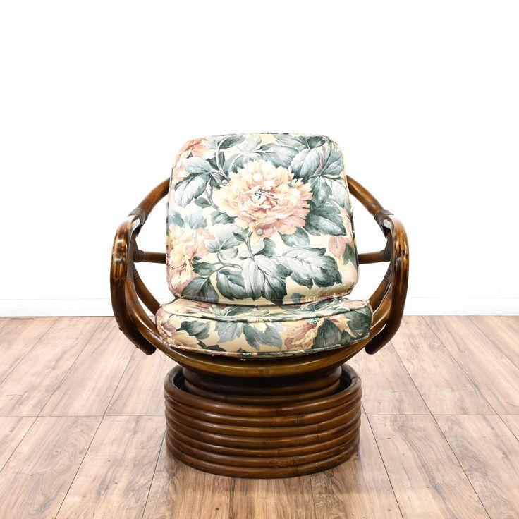 This rocking chair is featured in a durable rattan with a pecan finish. This bohemian style accent chair has large floral print upholstery, hoop-shaped design, and stacked circular base. Perfect for adding tropical vibes to a room! #bohemian #chairs #accentchair #sandiegovintage #vintagefurniture