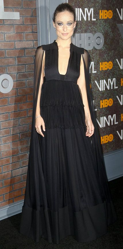 Olivia Wilde dialed up the drama at the Vinyl premiere in a black Valentino gown with a plunging neckline and a sheer ground-grazing cape. Eva Fehren jewelry and a black netted headpiece added to the allure.