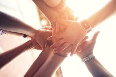 Group of people place hands on top of each other's stock photo