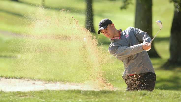 A California University of Pennsylvania Professional Golf Management student chips onto the green from a bunker