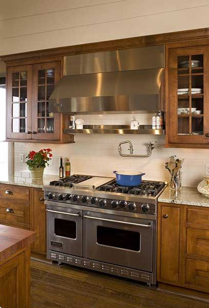 """ A 48-inch Viking range with griddle, a matching stainless steel ventilation hood, a potfiller faucet and a stainless steel shelf for spices make this kitchen a cook's dream. "" via @kitchens.com Visit www.vikingrange.com to see additional colors, sizes, and fuel options."