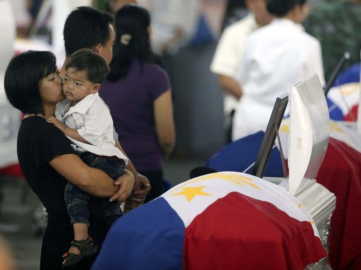 Com o filho no colo, viúva vela o corpo de agente especial morto em combate nas Filipinas. No último domingo (25), 44 policiais morreram em confronto com a Frente Moro de Libertação Islâmica, na província de Maguindanao (Foto: Bullit Marquez/AP) - http://epoca.globo.com/tempo/filtro/fotos/2015/01/fotos-do-dia-30-de-janeiro-de-2015.html