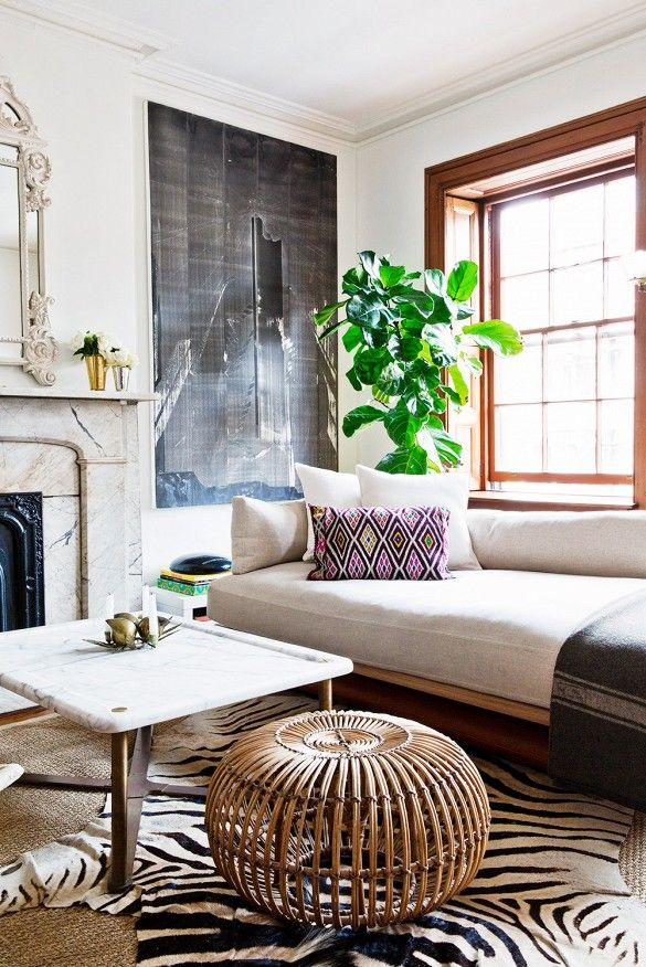 Midcentury-inspired sofa and classic marble mantel, with timeless elements, like a zebra hide rug and marble-top table